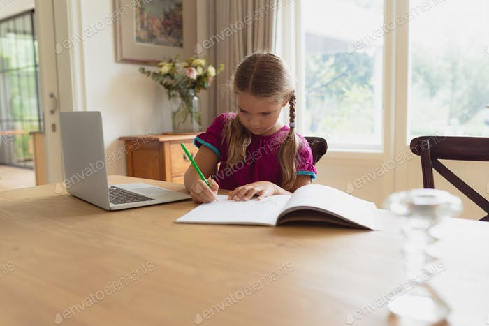 Front view of cute Caucasian girl doing homework at dining table in a comfortable home