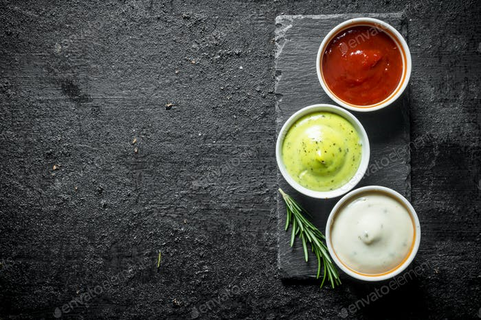 Guacomole sauce, tomato sauce and mayonnaise on a stone Board with rosemary.