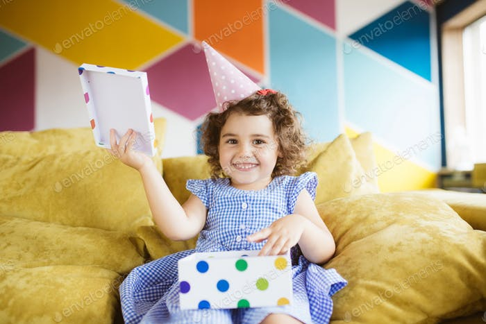 Beautiful smiling little girl with dark curly hair in birthday c