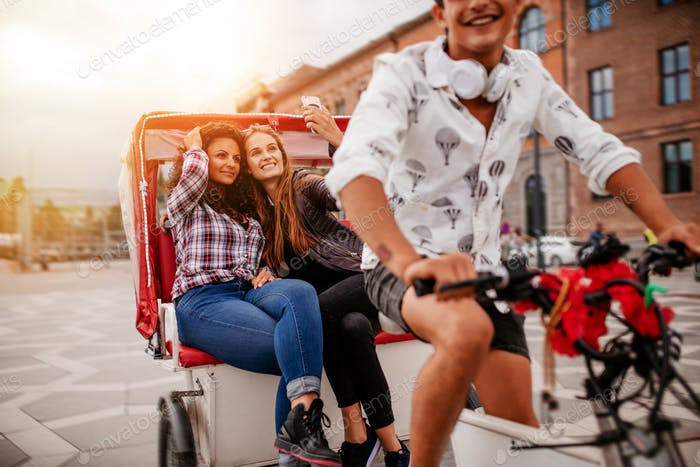 Female friends taking selfie on tricycle