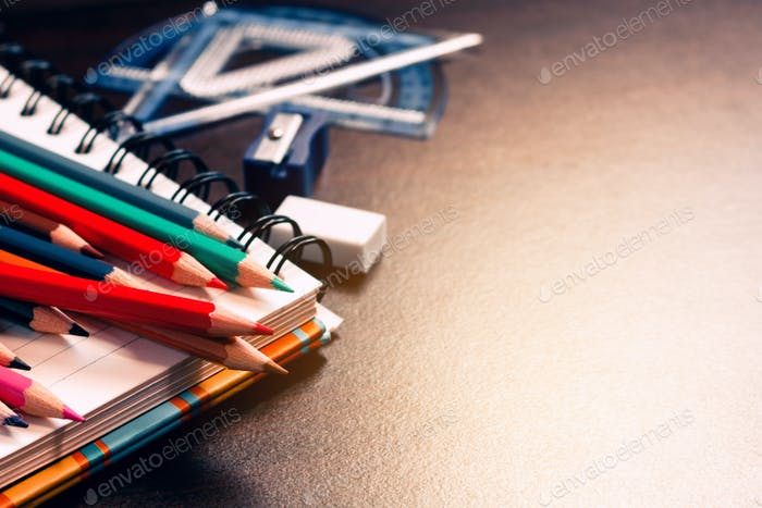 Color pencil on student table and notebook with education concept.