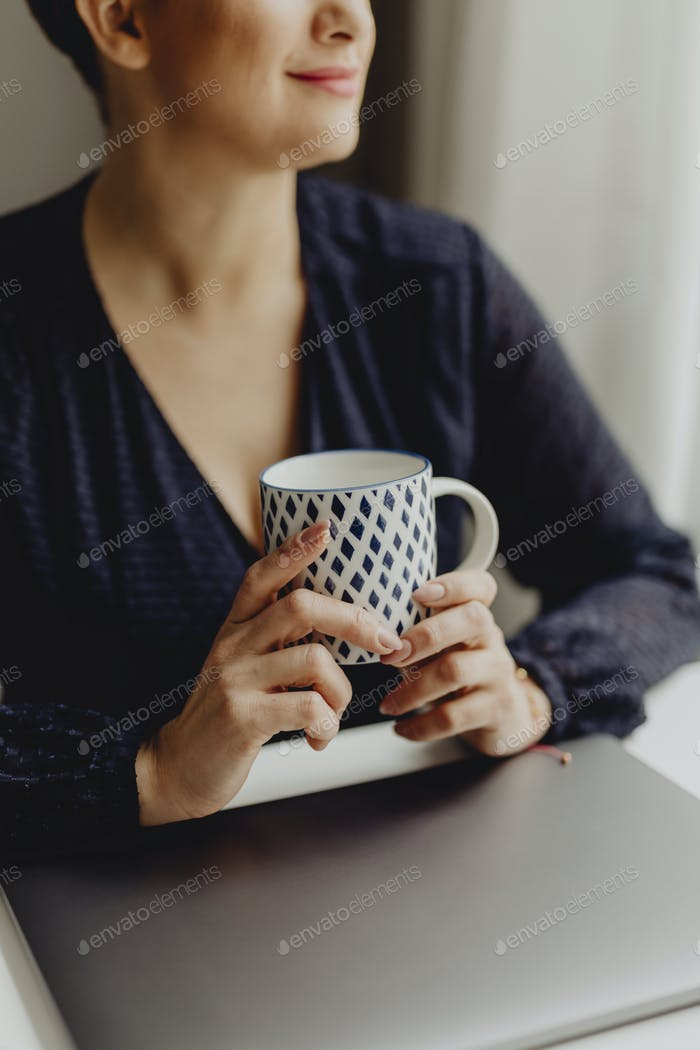 Drinking her morning coffee