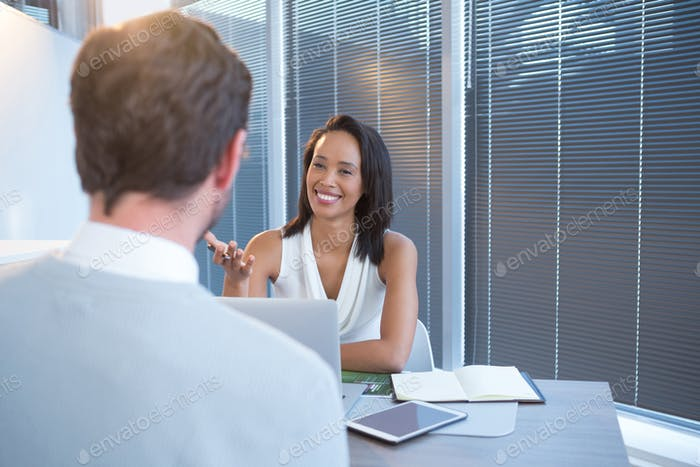 Business executives discussing at desk