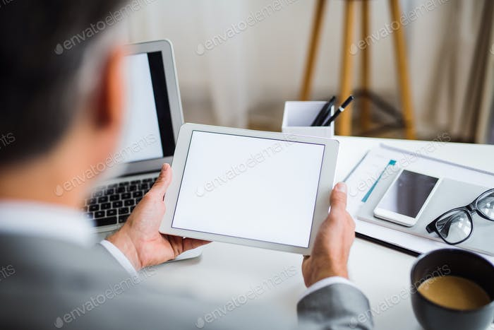 A midsection of businessman sitting at the table, using tablet. A rear view. Copy space.