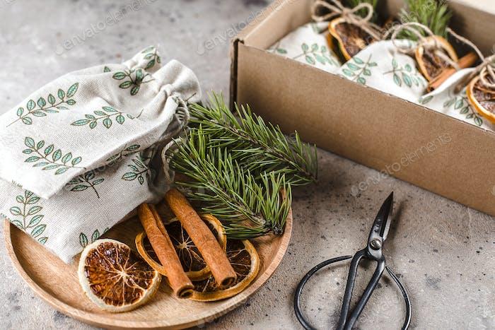 Dekorieren von Weihnachtsgeschenken durch trockene Orande, Zimt, Tanne. Umweltfreundliche Textil-Geschenkverpackung
