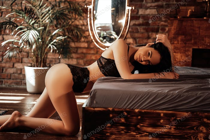 Luscious and graceful woman posing, wearing lingerie near big bed in a luxury bedroom