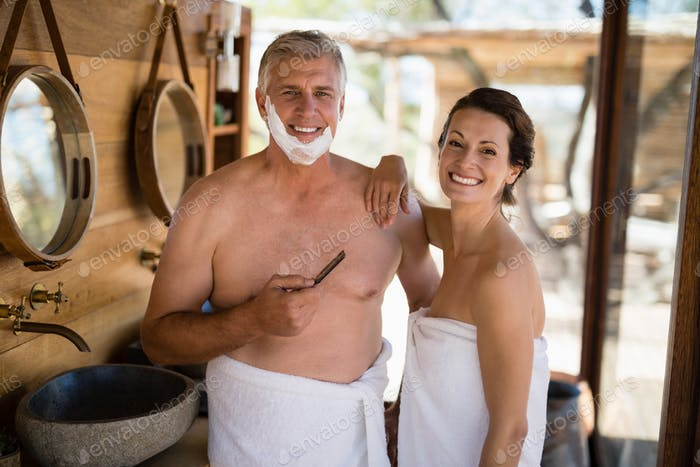 Portrait of couple smiling while shaving in cottage