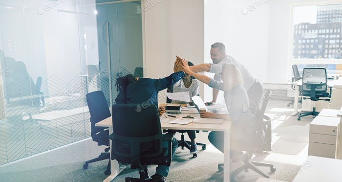Smiling office workers high fiving together during a meeting