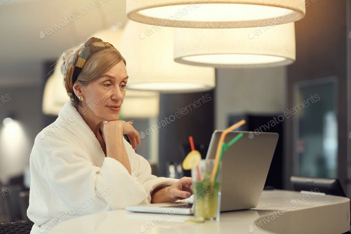 Elegante Senior Frau mit Laptop im SPA Resort