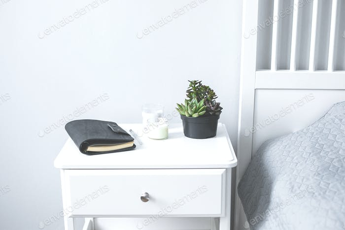 Tiny succulents, candles and black notebook on bedside table in the bedroom in scandinavian style