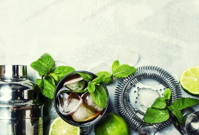 Alkoholischer Cocktail mit Rum, Cola, Eis und Minze, Barwerkzeuge