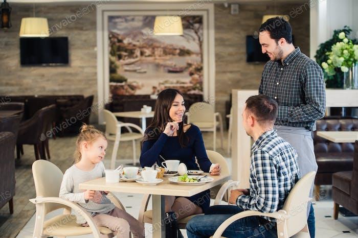 Familie, Elternschaft, Technologie, Menschen Konzept - glückliche Mutter, Vater und kleines Mädchen zum Abendessen