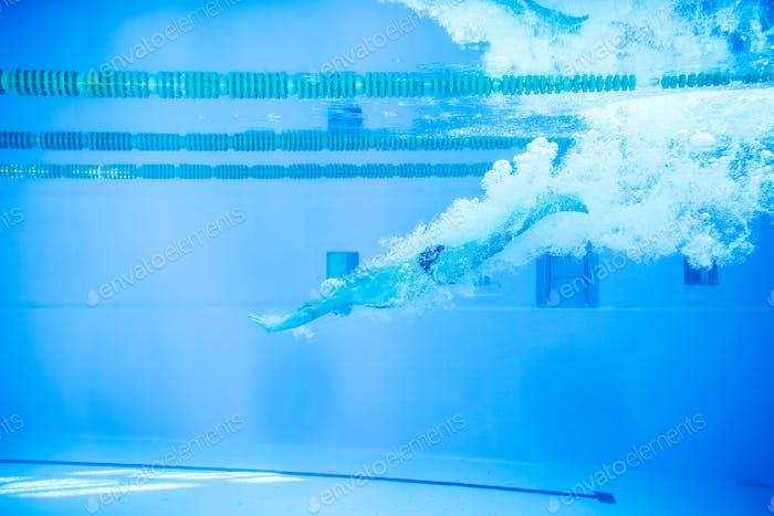 Senior man jumping in the swimming pool.