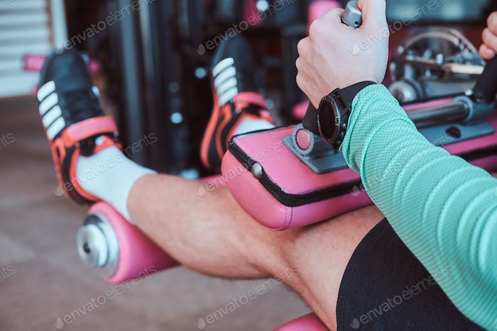Strong active man is doing legs exercises on training apparatus in gym