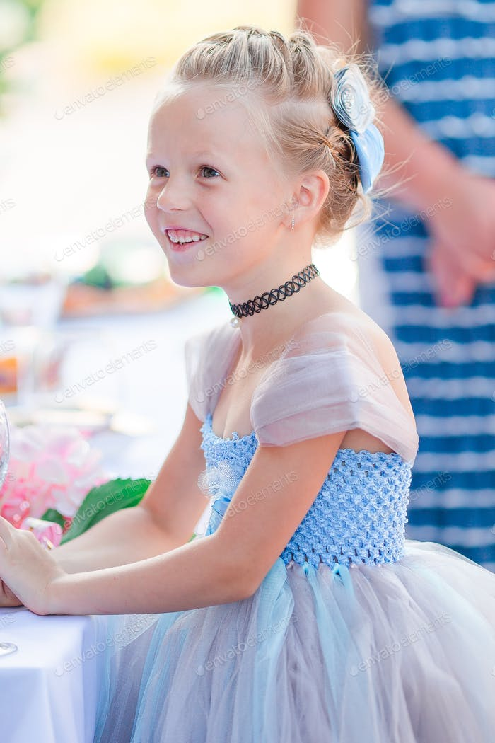 Adorable little girl in amazing dress at a wedding ceremony outdoors