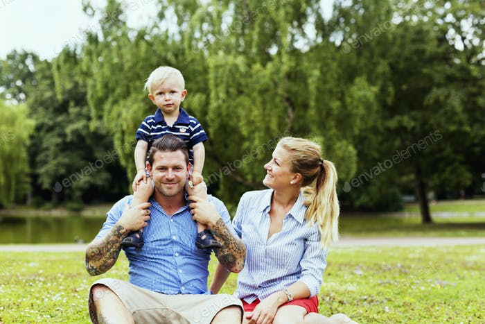 Happy family of three relaxing in park