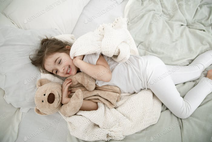 A cute little girl is sleeping in a bed with a Teddy bear toy .