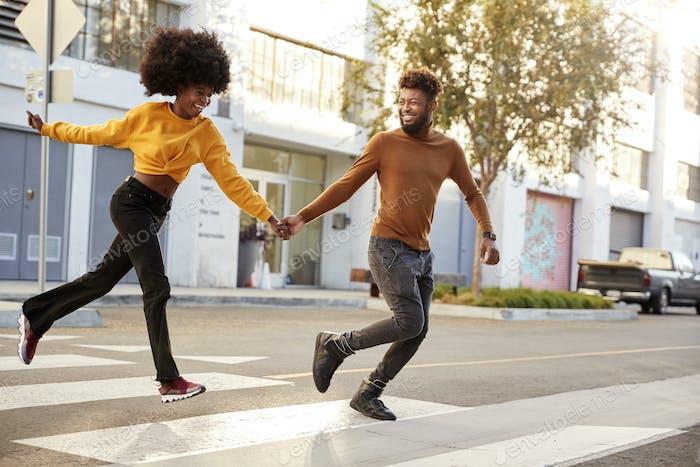 Moda joven pareja negro corriendo a través de una Ciudad calle tomados de la mano, Duración completa, de cerca