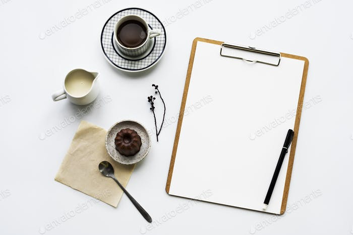 Aerial view of paper clipboard with coffee cup and cake