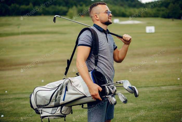 Handsome man playing golf on a golf course