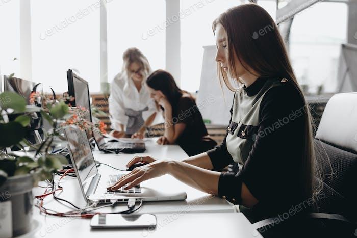 Mujeres hermosas jóvenes vestidas de acuerdo con dreskod oficina están Trabajo en los escritorios con una Ordenador