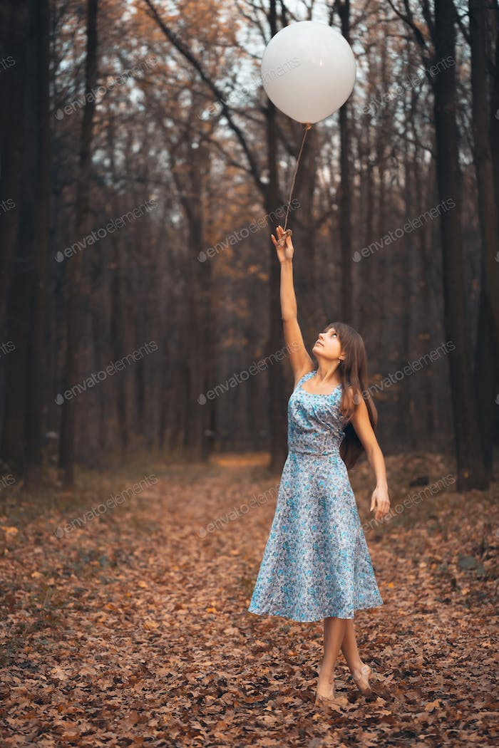 Girl with a balloon in the forest