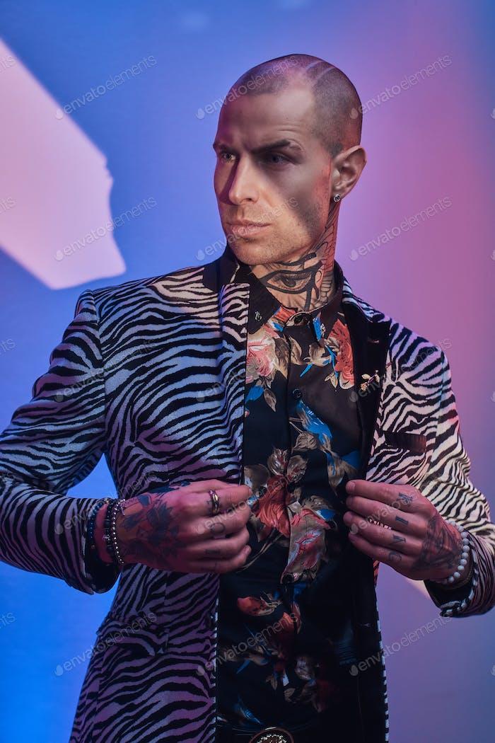 Modische tätowierte männliche Modell posiert in einem Studio
