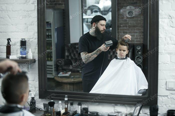 Children hairdresser cutting little boy against a dark background.