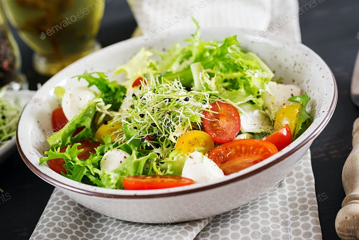Vegetarian salad with cherry tomato, mozzarella and lettuce. Italian cuisine.
