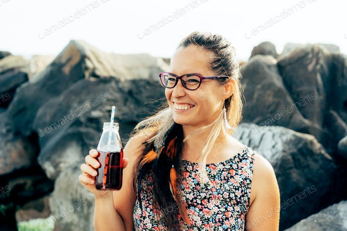 Young happy brunette wearing glasses holding a bottle with a drink and having fun.