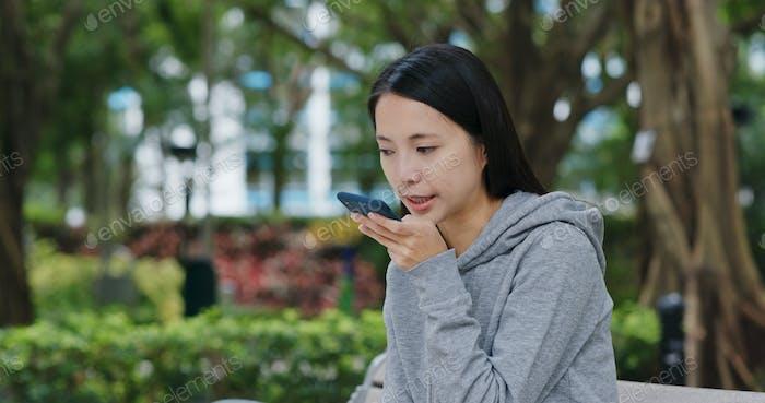 Woman send audio message in city park