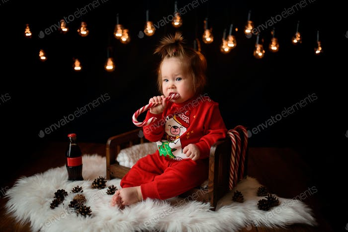 7 month old girl in a red Christmas costume on a background of retro garlands sits on a fur.