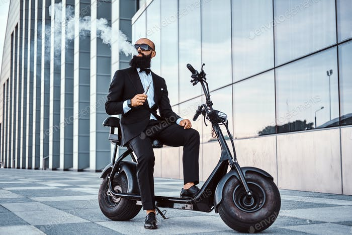 Элегантный бизнесмен курит, сидя на электро велосипеде
