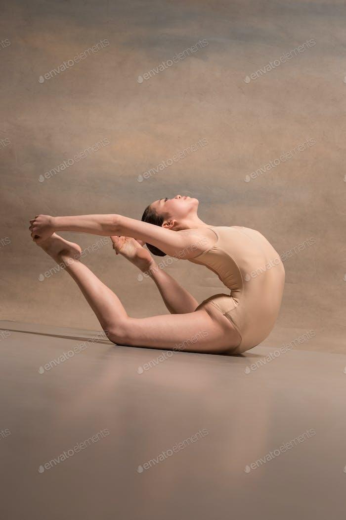 The female ballet dancer posing over gray background