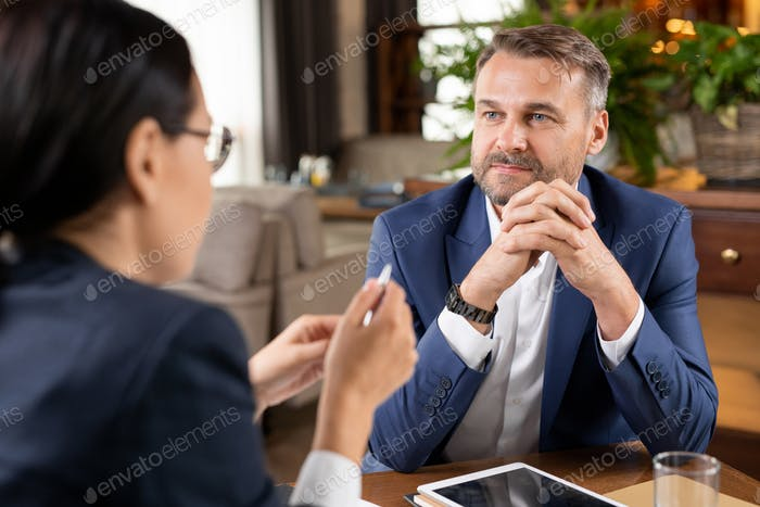 Serious entrepreneur in formalwear listening to young partner or colleague