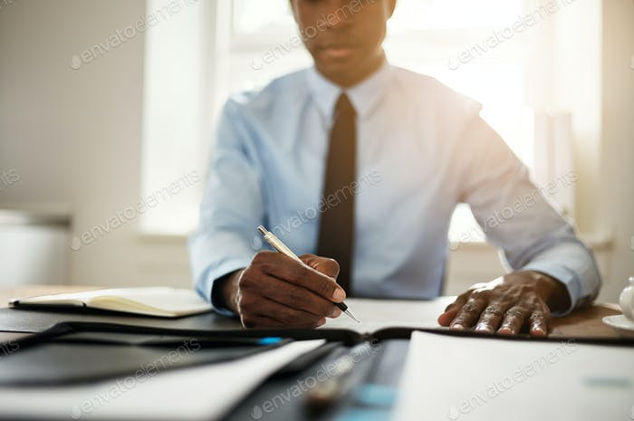 Young executive signing contracts at his office desk