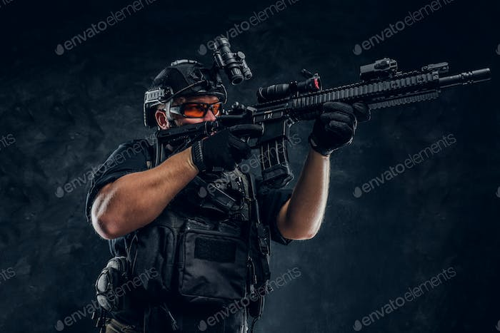 Special forces soldier wearing body armor holding an assault rifle. Studio photo