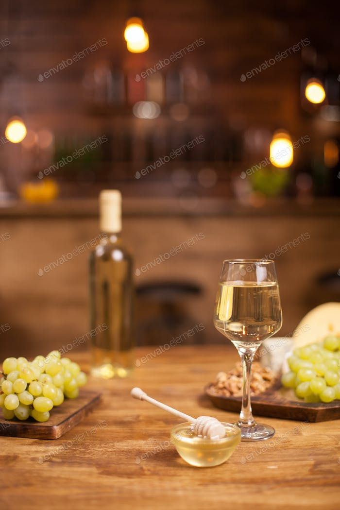 Bowl of golden honey jar next to fresh grapes and wolnuts over a wooden table