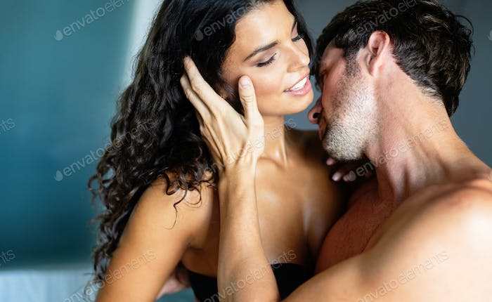 Sexy young couple kissing and playing in bedroom