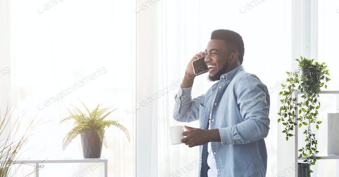 Alegre hombre afroamericano hablando por teléfono y bebiendo café