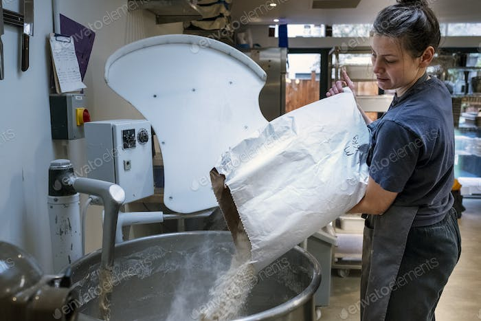 Woman wearing apron standing in an artisan bakery, pouring flour into industrial mixer.