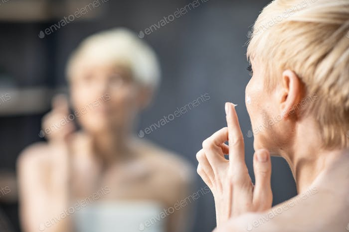 Lady Applying Face Cream Standing Back To Camera In Bathroom