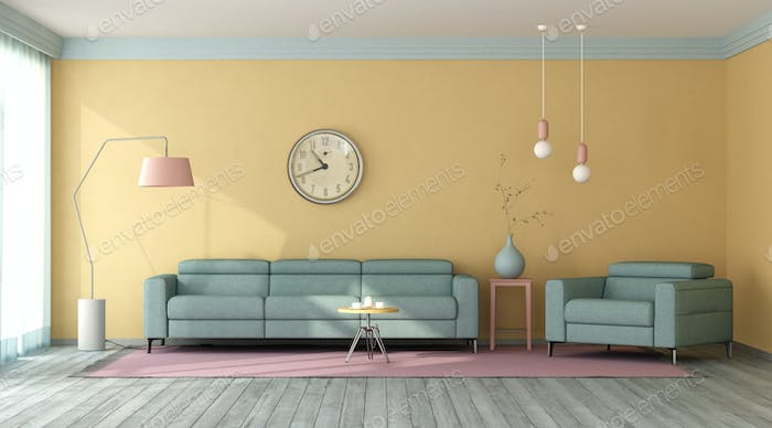 Blue sofa and armchair in a living room with yellow walls