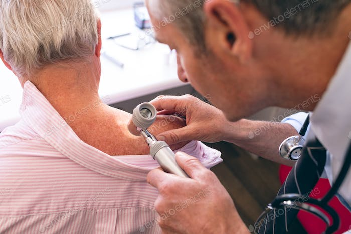 Matured male Caucasian dermatologist examining senior patient through dermatoscopy at clinic
