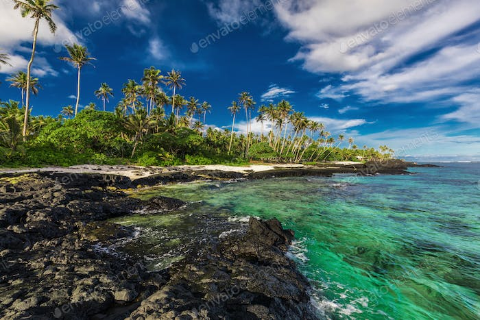 Beach with coral reef and black volcanic rocks on south side of