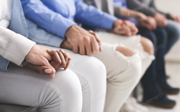 Group of people holding hands, sitting in row