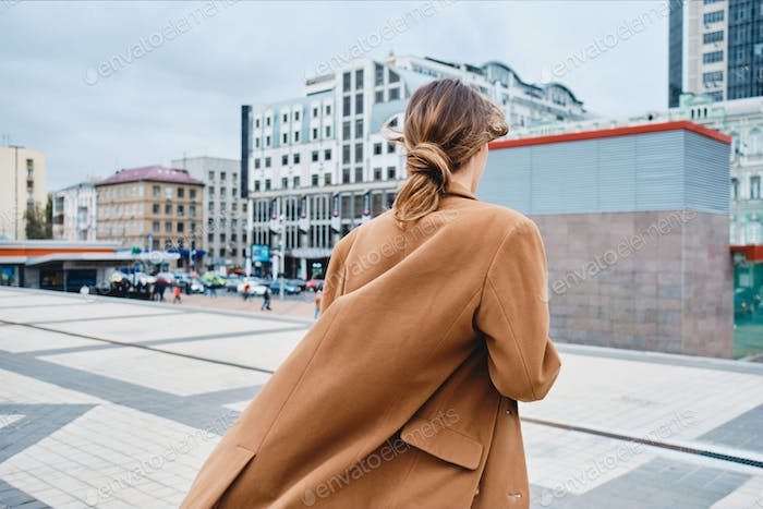 Back view of young stylish woman in coat confidently walking through city street
