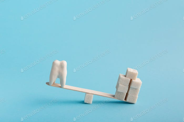 Healthy tooth and sugar balancing on seesaw swing