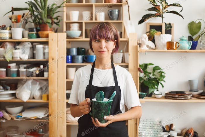Pretty girl with colorful hair in black apron and white T-shirt holding handmade bowl in hands