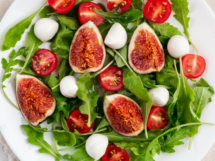 Fresh salad with figs, tomatoes, cucumbers, arugula, mozzarella, oil. top view, macro close up